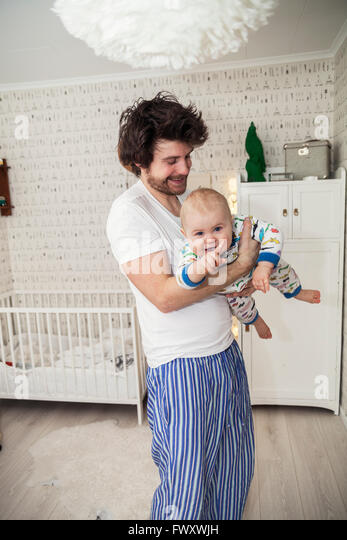 Sweden, Father holding son (12-17 months) - Stock Image