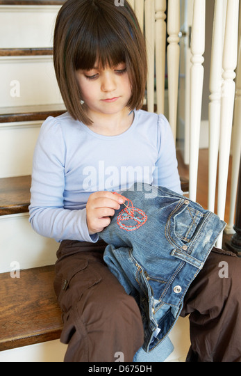 child sewing peace sign - Stock Image