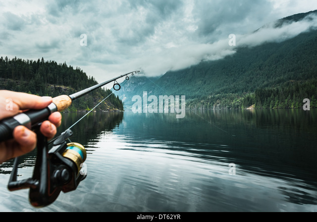 Man holding fishing rod close-up, Buntzen Lake, British Columbia, Canada - Stock Image