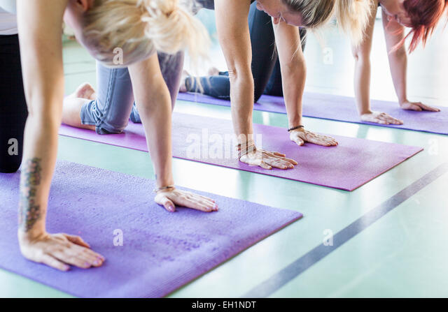 Women exercising on yoga mats in health club - Stock Image