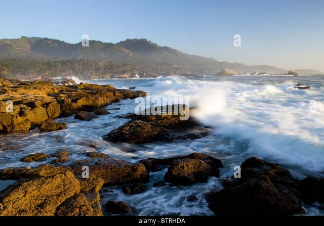 Waves crash along the shore at Point Lobos State Park, California. - Stock Image