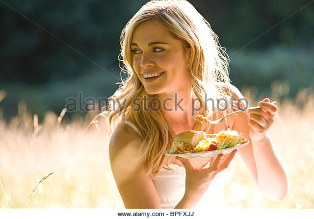 A young woman sitting on the grass, eating - Stock-Bilder