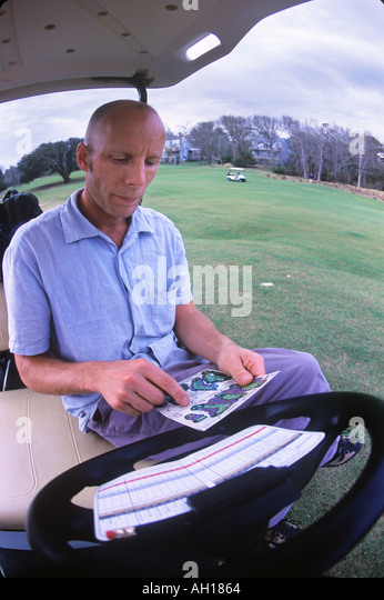 Young man planning course strategy in golf cart - Stock Image