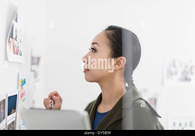 Young woman looking at images on wall - Stock Image