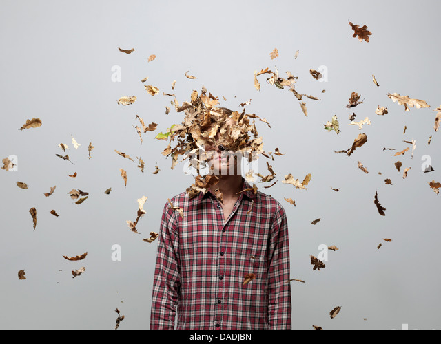 Young man with face obscured by leaves - Stock Image