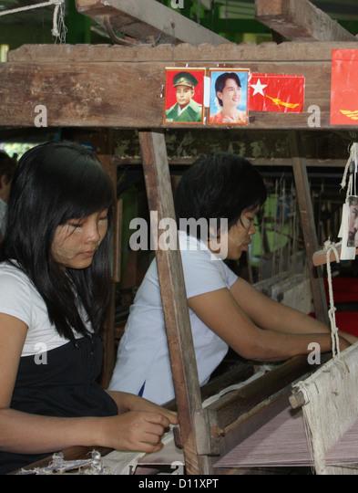 Women work at the showroom of the silk weaving factory in Mandalay (Amarapura Township), Myanmar, 25 October 2012. - Stock-Bilder