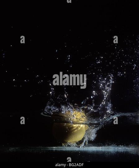 Splashing fruit in clear water. - Stock-Bilder