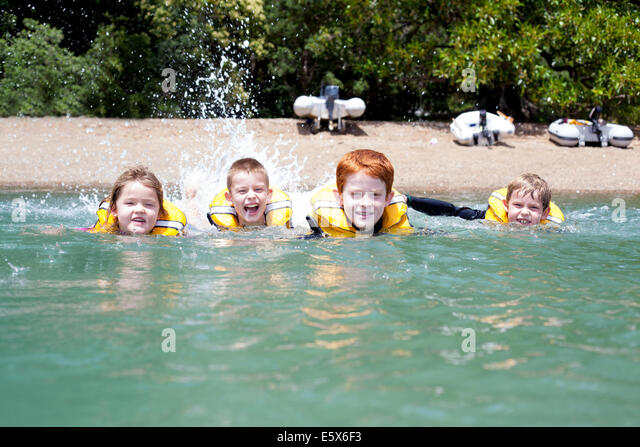 Brothers and sister in a row swimming in sea - Stock Image