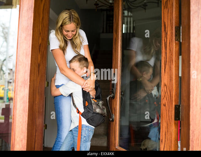 Boy (6-7) hugging mother before leaving for school - Stock Image
