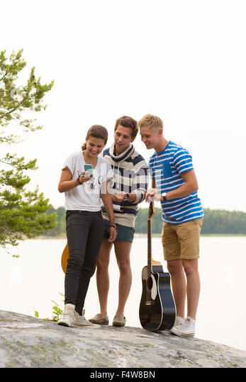 Friends, two young men and girl (12-13) standing at seaside and looking at smartphone - Stock Image