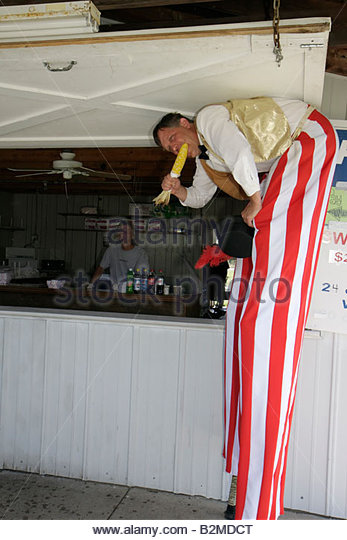 Wisconsin Kenosha Kenosha County Fairgrounds The Ultimate Kid Fest family event carnival stilt walker eat corn bent - Stock Image