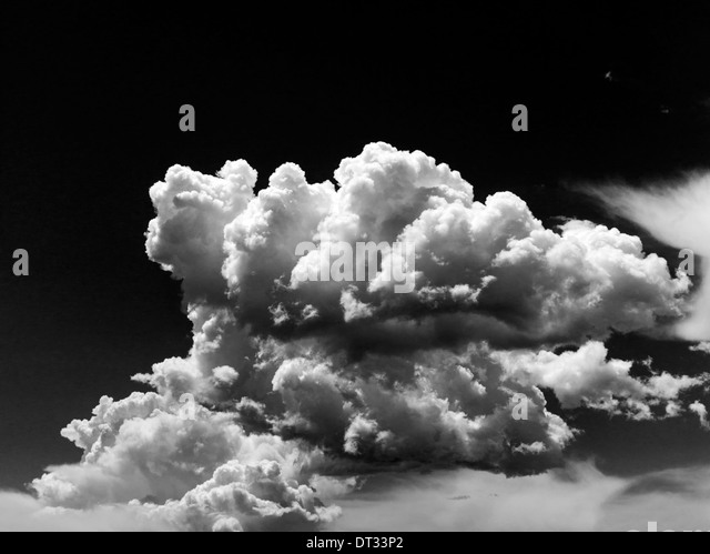 Black & white view of white puffy cumulus clouds against clear Colorado sky - Stock Image