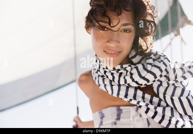 Young woman on yacht wearing striped scarf - Stock Image