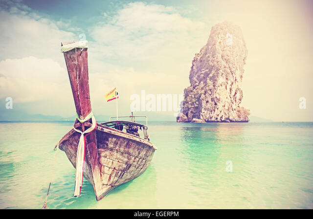 Vintage filtered picture of wooden boat on a tropical island. - Stock Image