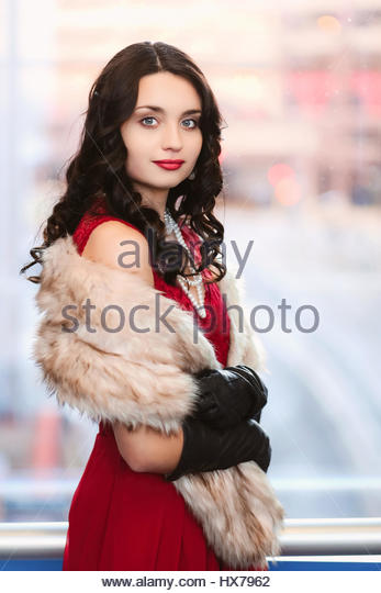 Young woman in red dress and fur - Stock Image
