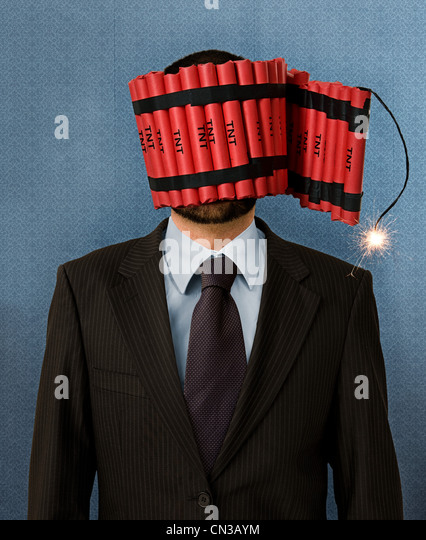 Businessman wrapped in dynamite - Stock Image