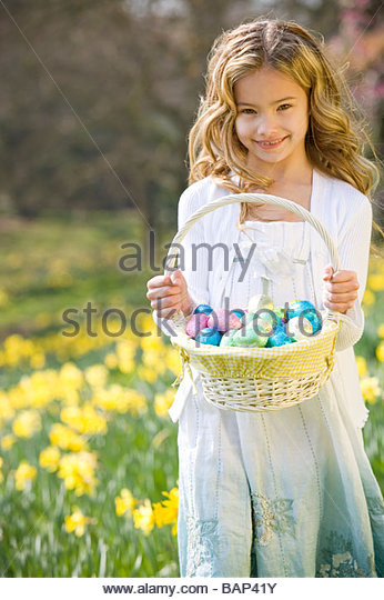 A young girl holding a basket full of Easter eggs, smiling, - Stock Image