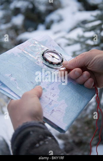 A male hiker checks his location with a compass and topographic map. - Stock Image