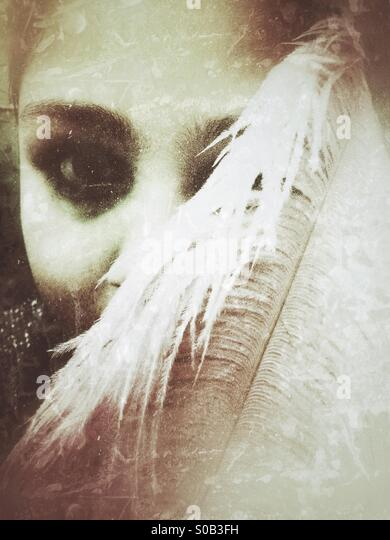 Girl hiding face with feather - Stock Image