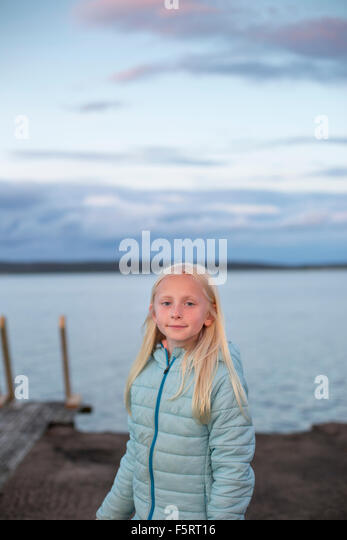 Sweden, Halland, Onsala, Portrait of girl (10-11) in front of lake - Stock Image