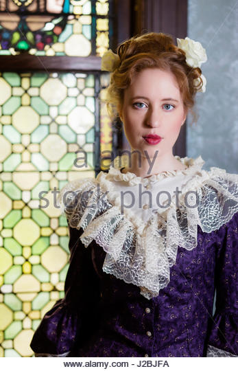 Red haired Victorian woman standing in front of stained glass window - Stock Image