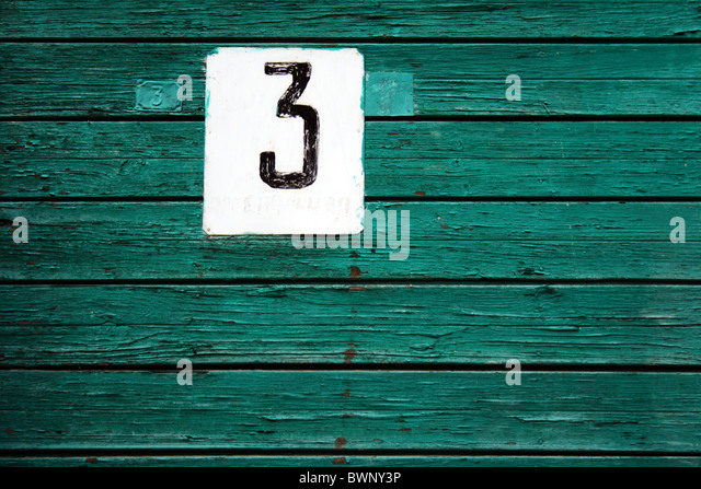house label No 3 on green wooden plank wall - Stock Image
