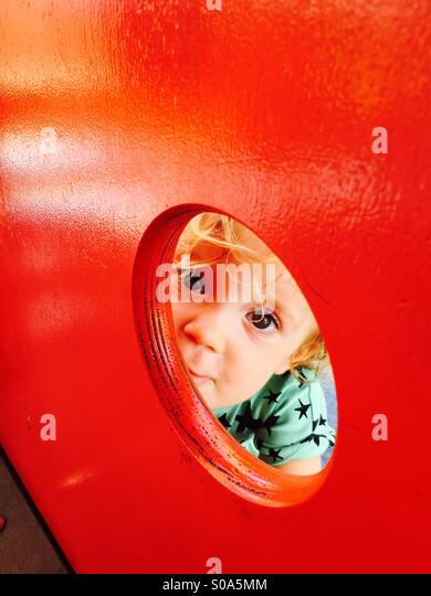 Hello little cheeky girl! Have a play and a smile with your peekaboo ways. - Stock Image