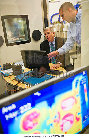 Robert Shaw, right, with Arkansas Power Electronics International demonstrates user interface for equipment to U.S. - Stock Image