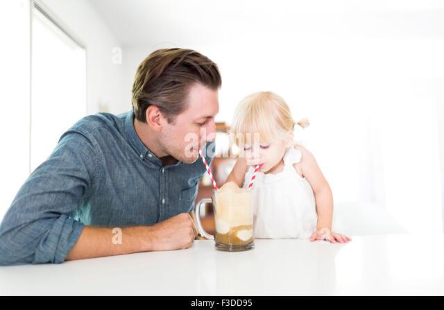 Father drinking milkshake with daughter (2-3) - Stock Image