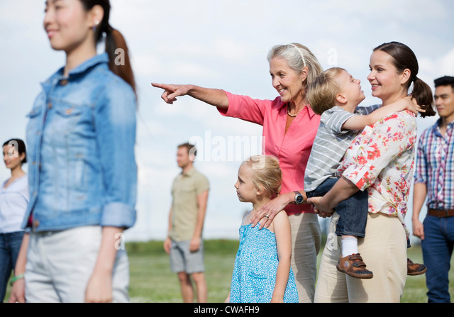 Group of people outdoors, focus on senior woman and family - Stock Image