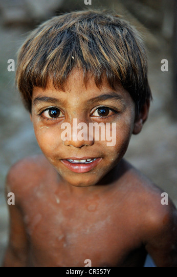 Portrait, cheeky boy with his face and body smeared with clay, the boy works with his family under the slavery-like - Stock Image