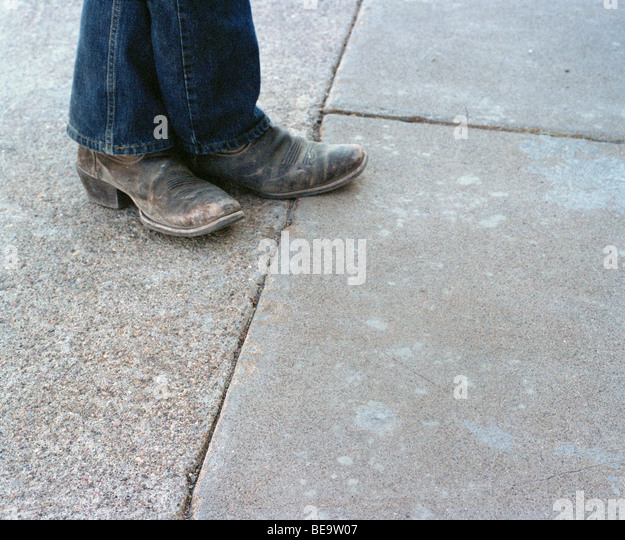 Close up of weathered cowboy boots and denim jeans - Stock-Bilder