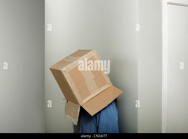Businessman wearing cardboard box over head - Stock Image