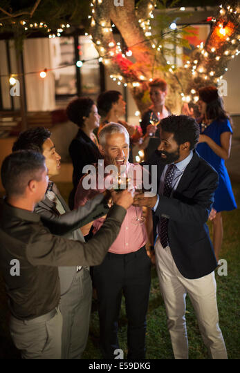 Men toasting each other at party - Stock Image