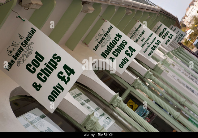 UK, England, Devon, Ilfracombe, promenade, inexpensive take away fish and chips signs - Stock Image