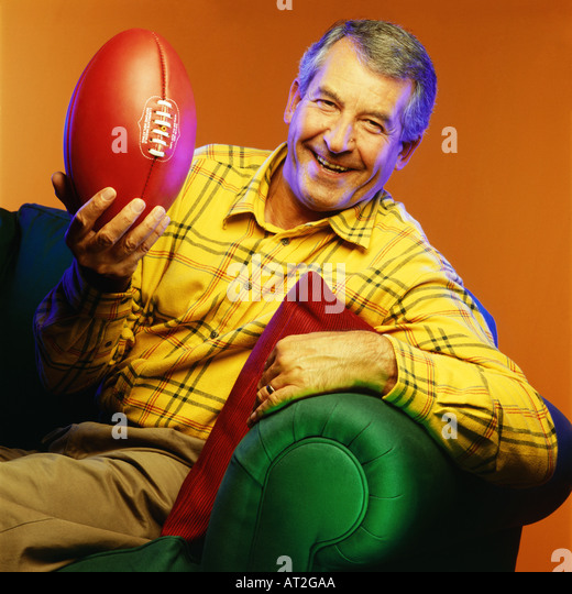 A man sitting on a sofa holding a rugby ball - Stock Image
