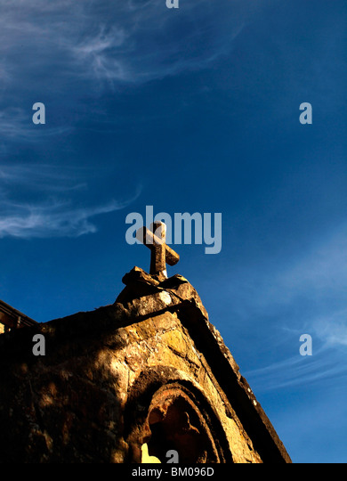 Ancient Cross on a church roof against blue sky - Stock Image