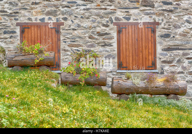 two windows and three flower boxes on the sloping lawn - Stock Image
