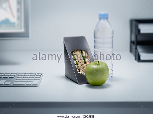 Sandwich, apple and water on office desk - Stock Image