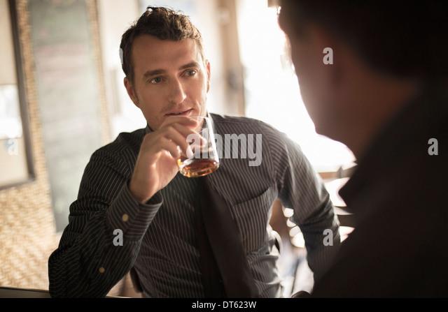 Two businessmen having a drink in wine bar - Stock-Bilder