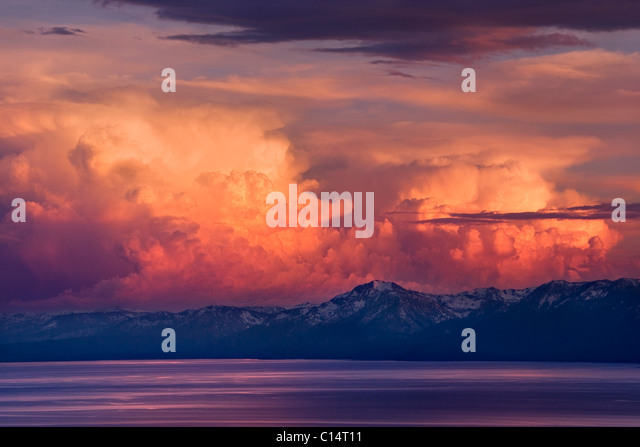 Alpenglow thunderheads at sunset over Lake Tahoe and the snow covered Sierra mountains - Stock Image