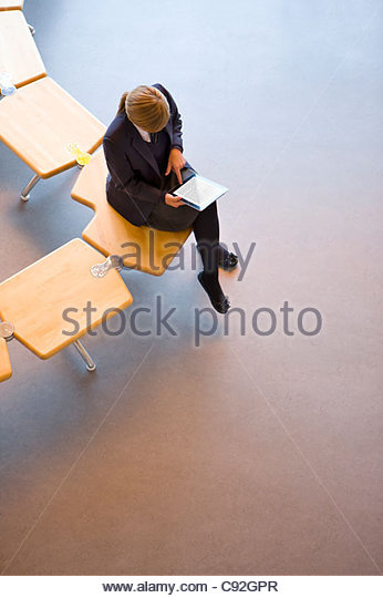 Female student in school uniform using digital tablet on bench - Stock Image