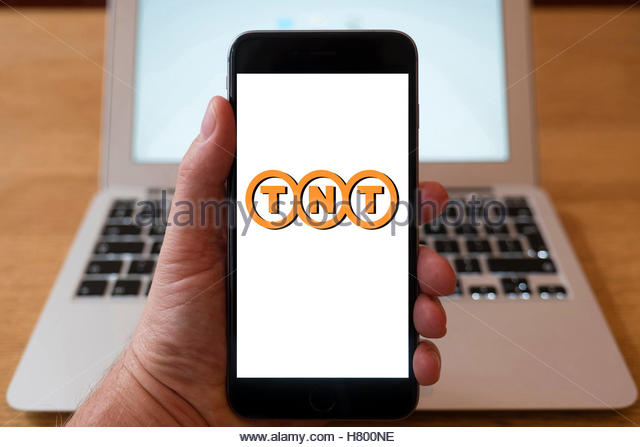Using iPhone smartphone to display logo of TNT the international courier delivery services company - Stock Image