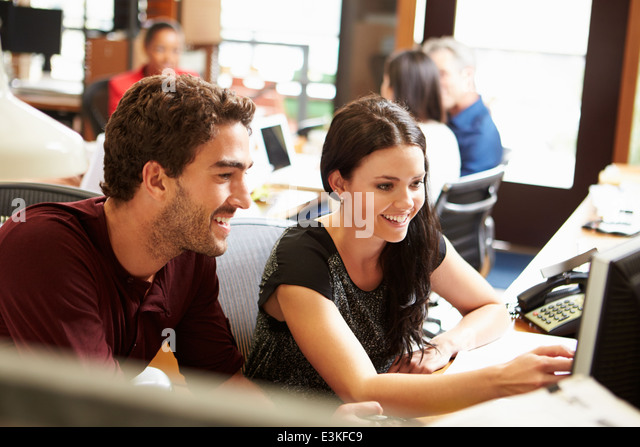 Two Colleagues Working At Desk With Meeting In Background - Stock Image