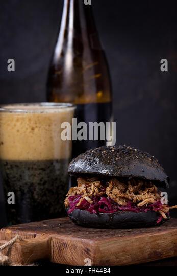 Black burger with dark beer - Stock Image