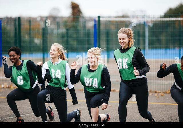 Female netball players warming up on netball court - Stock Image