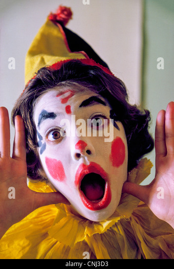A young girl dresses up as a colorful circus clown to go trick-or-treating during the annual Halloween celebration - Stock-Bilder