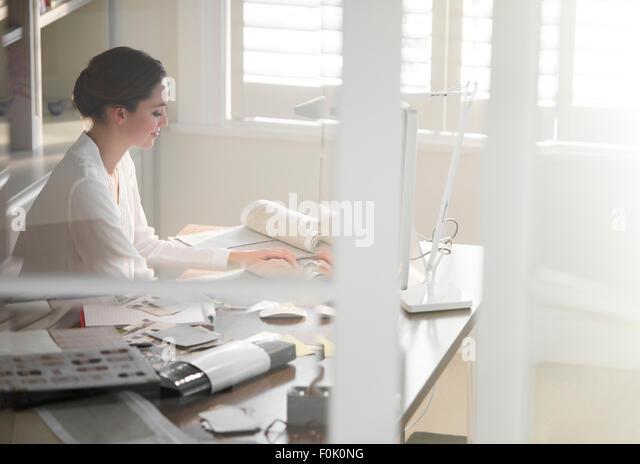Interior designer working at computer in home office - Stock-Bilder