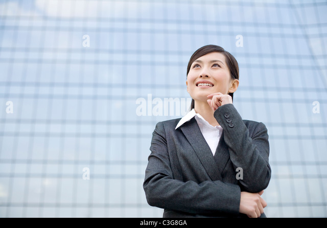 Young businesswoman standing in front of a tall building - Stock Image