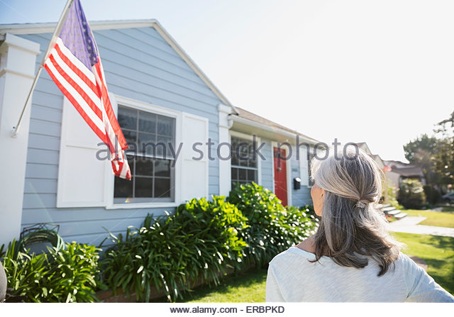 Senior woman looking up American flag and house - Stock Image